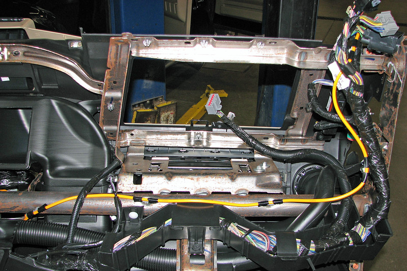 Wiring harnesses on the modern automobile are extremely large and complex thanks to the number of on-board computerized system components.The photo above looks at the right hand side of the instrument panel where the passenger's air bag sits.  The wiring harness in question encompasses all of the exposed wires seen in the photo.