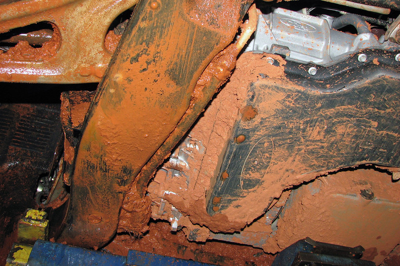 The photos above and below look toward the front of the van.  Mud can be seen filling just about every open space or small gap from the transmission pan to the engine cradle.  The power steering cooler hose is engulfed in mud as well.  Apparently, this Ford Freestar has been mistaken for an off-road vehicle that has 4-wheel drive.  It looks like someone from the department had to make a trip to one of the off-site research facilities, and hopped in the first vehicle he/she saw.