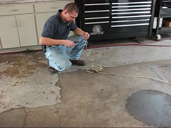 """At UGA, we still have several of the old style """"in-floor"""" twin post lifts.  Phil raised the lift, placed the airbag with wiring hooked to it in the post valley, then lowered the lift.  This way, the airbag can't go anywhere.  Then, all he needed was 12 Volts.  Click the video above, then click """"play"""" to see the process."""