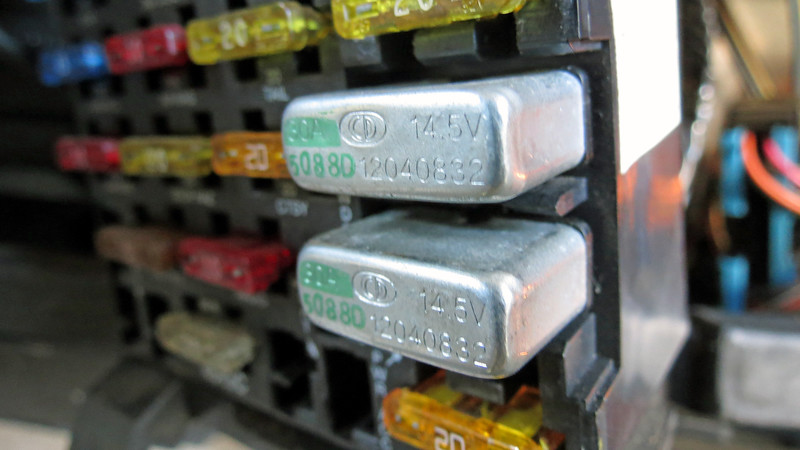"""Components that draw a lot of current will sometimes be protected by a circuit breaker instead of a regular fuse.  A circuit breaker will """"trip,"""" (i.e. become open so current flow is interrupted), when a fault is detected.  But unlike a fuse that can only be used one time, a circuit breaker will automatically reset when the fault is corrected.  In the photo above, the interior fuse block on this Buick contains two silver circuit breakers.  The power windows are protected by the upper 30 amp breaker.  <br /> <br /> I can't say the YOW I let out from being burned by the circuit breaker was loud enough for the whole shop to hear.  But let's just say that I was quite surprised by how extremely hot the breaker was.  This would seem to indicate that I was dealing with a short circuit.  Figuring out where a short is located can get interesting.  A quick check of the wiring diagram for the power windows provided me with a starting point."""
