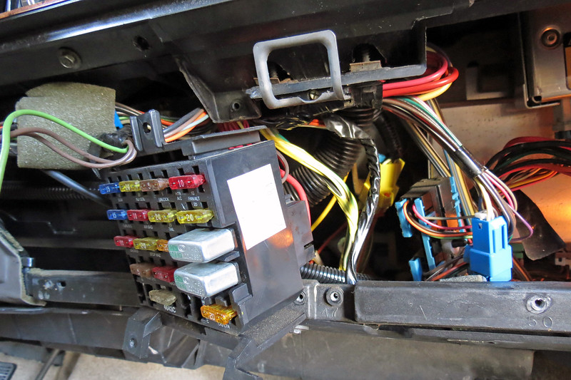 "According to the wiring diagram, power comes from the fuse box seen in the photo above and is fed to all four power windows via a brown wire.  I suspected my problem was a ""short circuit,"" meaning the brown wire was touching ground somewhere along one of those paths.  To confirm this, I removed the circuit breaker from the fuse block, (without getting burned this time), and hooked my test light across the terminals in its place.  As expected, my test light lit up.  This meant my problem was with one of the brown wires somewhere between the fuse block and a window switch. <br /> <br /> In other words, I have to tear stuff apart until I find where this brown wire is touching ground.  There is no standard way to start tearing into things.  Since I had the fuse block already exposed, I decided to start there first.  Three fasteners hold it in place, along with several fasteners that hold the small glove compartment in place.  With those things out of the way, I didn't see anything that I would call obvious damage."