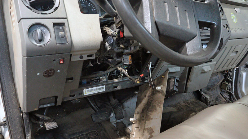 Thankfully, Ford makes this process much easier than it sounds and looks.  I first started by removing the trim cover below the steering wheel to gain access to the various electrical connectors that need to be disconnected, as well as the 4 nuts that hold the steering column in place.