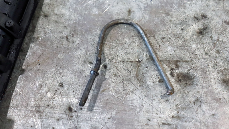 I had to remove the door latch assembly to find the missing door handle linkage rod.  The 180 degree bend seen in the photo above definitely should not be there !