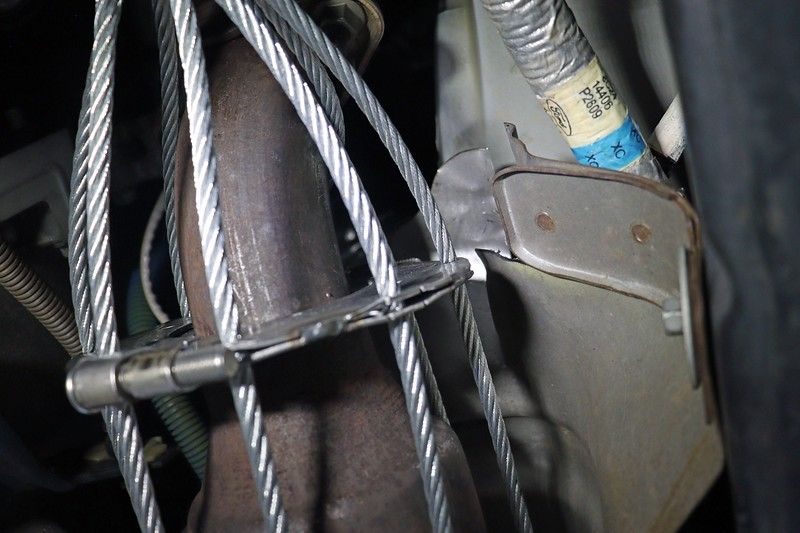 The clamp surrounds the pipe in front of the cat and is bolted in place with tamper-proof fasteners.