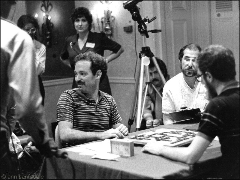 the 1983 North American Championship in Chicago at the Drake Hotel. Joel Wapnick smies after having just defeated Joe Edley to win the championship. Milt Wertheimer  annotated Wapnicks moves.  Worker Barbara Amster in background.  TV crew was recording game.