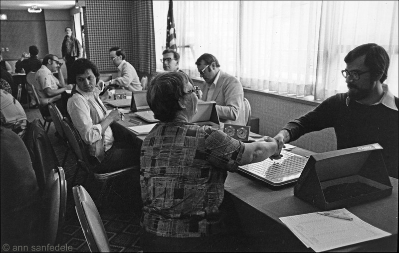 Day 1 of the 1978 North American Invitiational in New York.  From fron to back on the left side of the table are Roz Grossman, Ed Hepner, Mike Senkiewitz. John Ozag is shaking hands with Roz, behind him is Tim Maneth about to play Hepner.  Then Frank Kuehnrich is waiting for his opponent, and Dan Pratt is playing Senkiewitiz