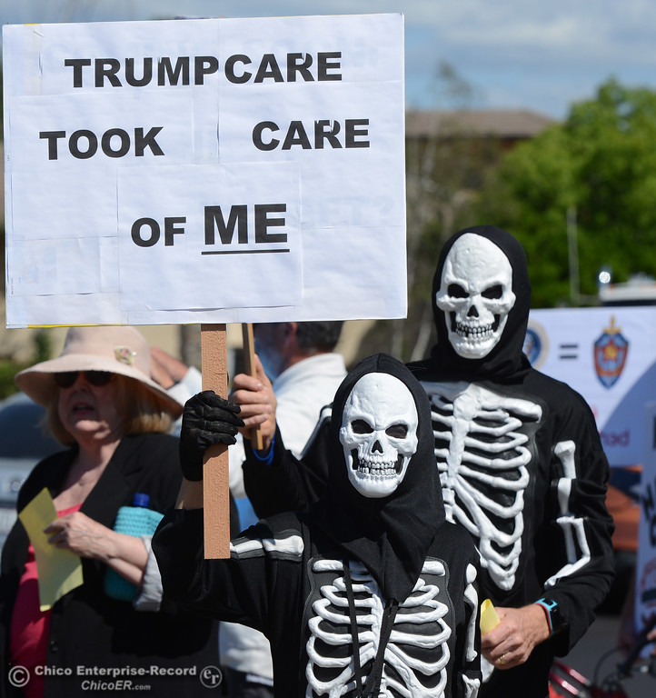 . Dressed as skeletons, Quincy residents Stephanie Leaf and Steve Ward, right, join protestors to wave signs and chant Friday, May 12, 2017, outside U.S. Representative Doug LaMalfa\'s office in Oroville, California. (Dan Reidel -- Enterprise-Record)