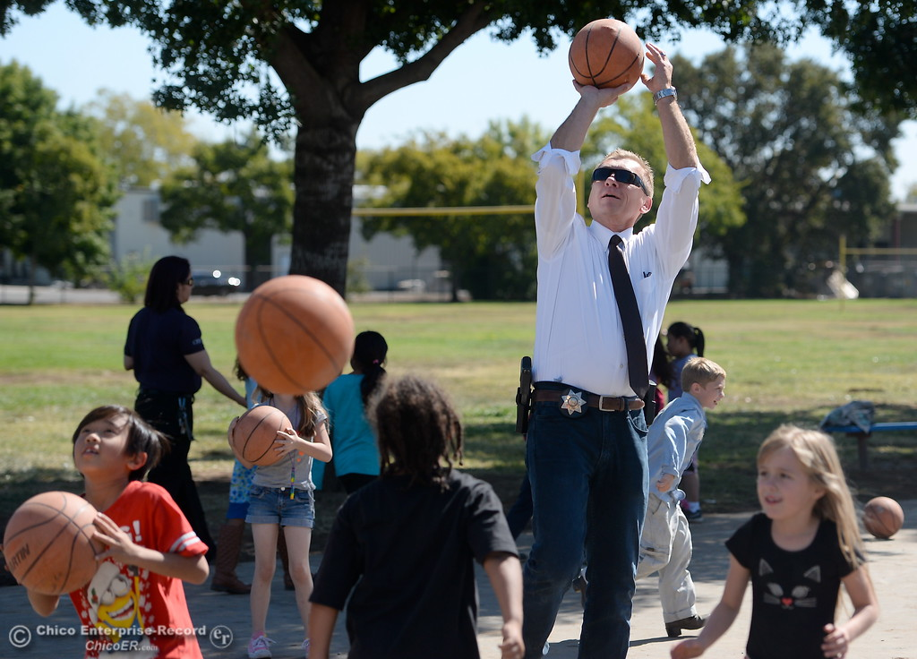 . Chico Police Department Detective Mark Bass plays basketball with students at Chapman Elementary School during the kids and cops event Wednesday Sept. 27, 2017.  (Bill Husa -- Enterprise-Record)