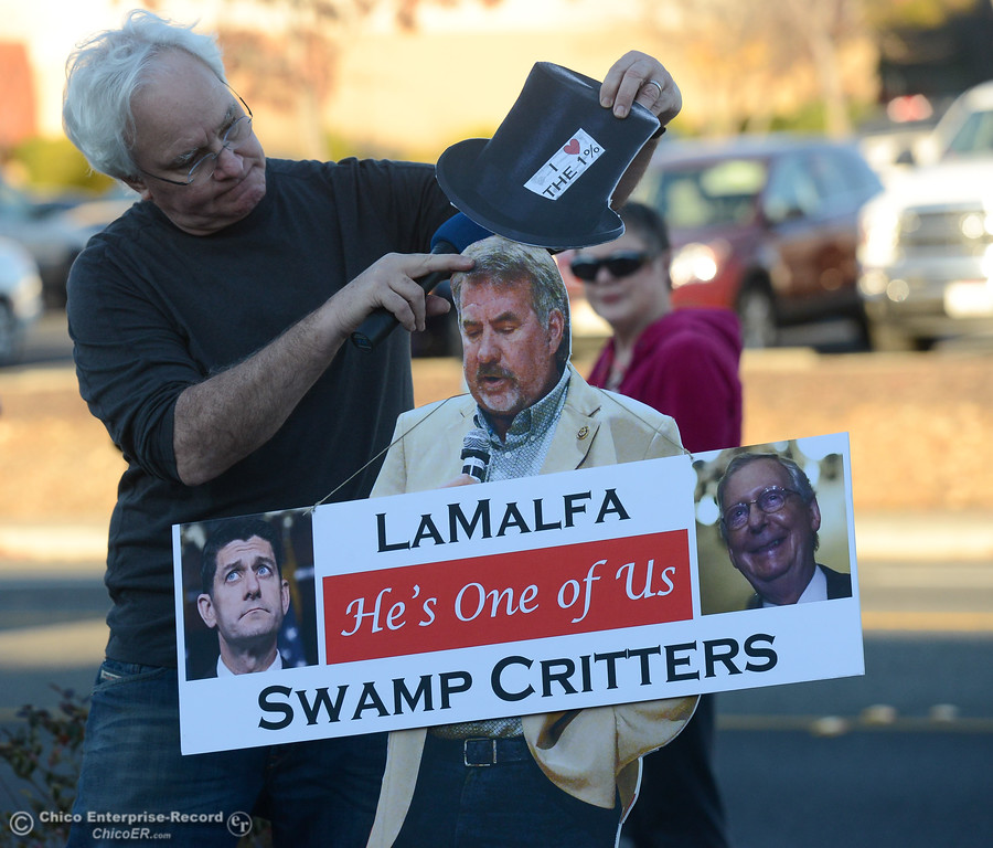 . Chico Indivisible member Jim McCabe of Durham places a top hat on a cut out of Congressman Doug LaMalfa as Chico Indivisible and the Democratic Action Club of Chico protest regarding the pending GOP tax bill and its associated health care funding cuts at the Oroville office of Congressman Doug LaMalfa Tuesday December 12, 2017 in  Oroville, California. (Emily Bertolino -- Mercury-Register)