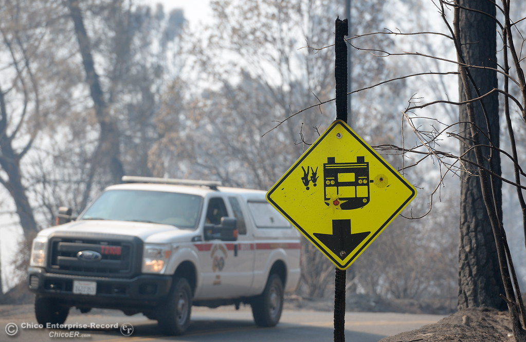 . A school bus sign hangs upside down as emergency vehicles drive along Lumpkin Road in the Ponderosa Fire area above Oroville, Calif. Wednesday Aug. 30, 2017.  (Bill Husa -- Enterprise-Record)
