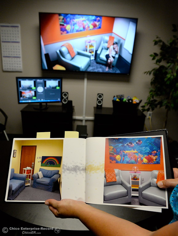 . Child Abuse Investigator Tonya Houston holds a photo showing the before and after of the new interview room inside of the observation room during the grand opening ceremony for the new Child Abuse Response Team room located in the former County Clerk space at 25, County Center Drive in Oroville, Calif. Tues. Aug. 22, 2017. Bill Husa -- Enterprise-Record)