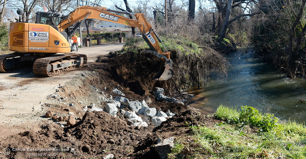 . Excavator Operator Shawn Bates places rocks brought in by dump trucks into the bank of Big Chico Creek along Bidwell Ave. in Chico, Calif. Thursday. The Butte County Public Works crew is working on the banks of Chico Creek that have eroded along side of Bidwell Avenue in beteween Rose Ave. and West Sacramento Ave. in Chico, Calif. Thurs. Jan. 5, 2016. Large and small rocks are used to create a barrier against further erosion. (Bill Husa -- Enterprise-Record)