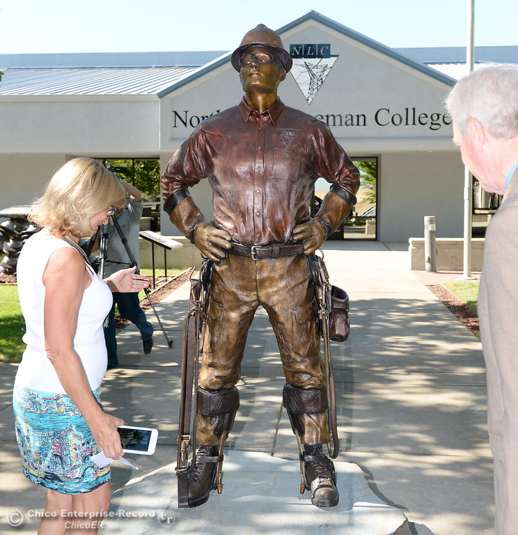 . At left, Mayor Linda Dahlmeier, right, District Attorney Mike Ramsey check out the new bronze statue during the unveiling of The Bronze Lineman statue at the Northwest Lineman College in Oroville, Calif. Wed. July 12, 2017. (Bill Husa -- Enterprise-Record)