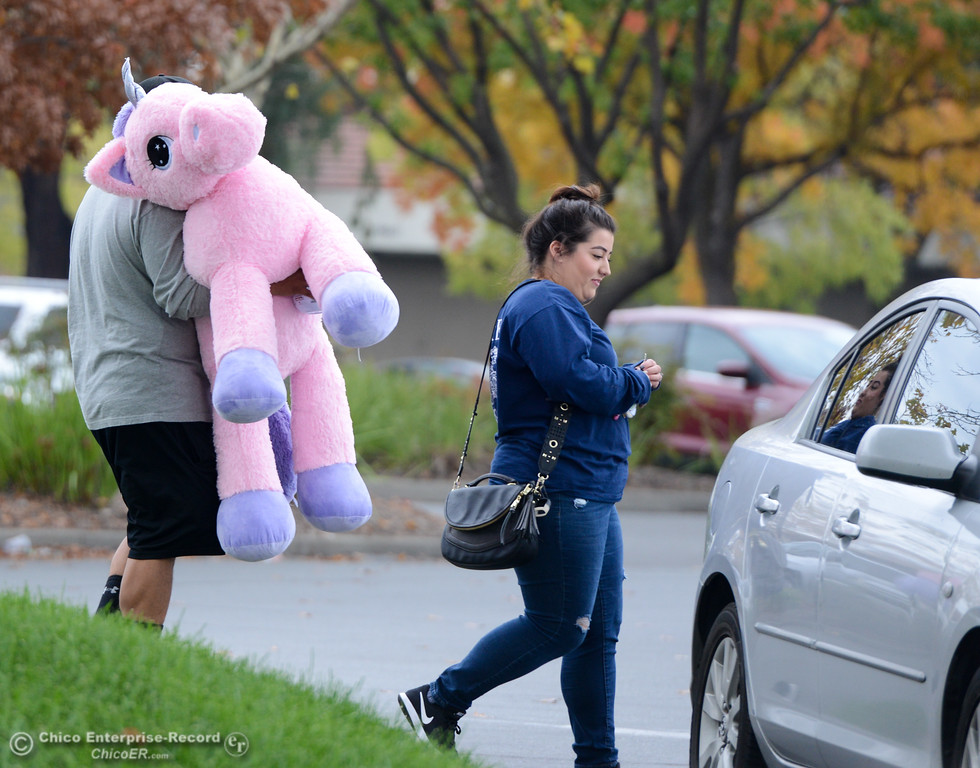 . A couple carries their large stuffed unicorn to their car on Black Friday November 24, 2017 in Chico, California. (Emily Bertolino -- Enterprise-Record)