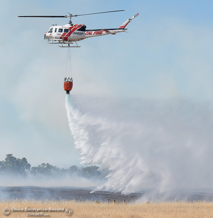 . Firefighters along with the help of a CAL FIRE Helicopter battle a grass fire of approx. 150 acres along Skyway just outside of Chico, Calif. Friday June 16, 2017. (Bill Husa -- Enterprise-Record)