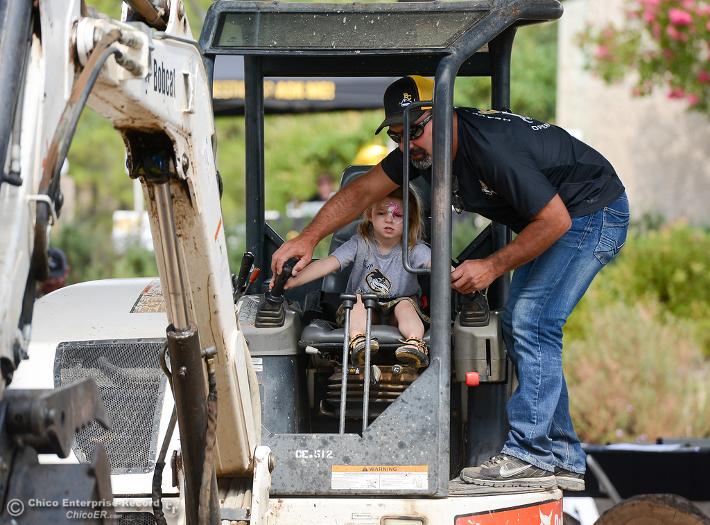. Sophie Bridges, 4, and heavy equipment instructor Tom Williams work a tractor to move bricks around during Butte College\'s 50th anniversary celebration September 15, 2017 at in Oroville, California. (Emily Bertolino -- Enterprise-Record)
