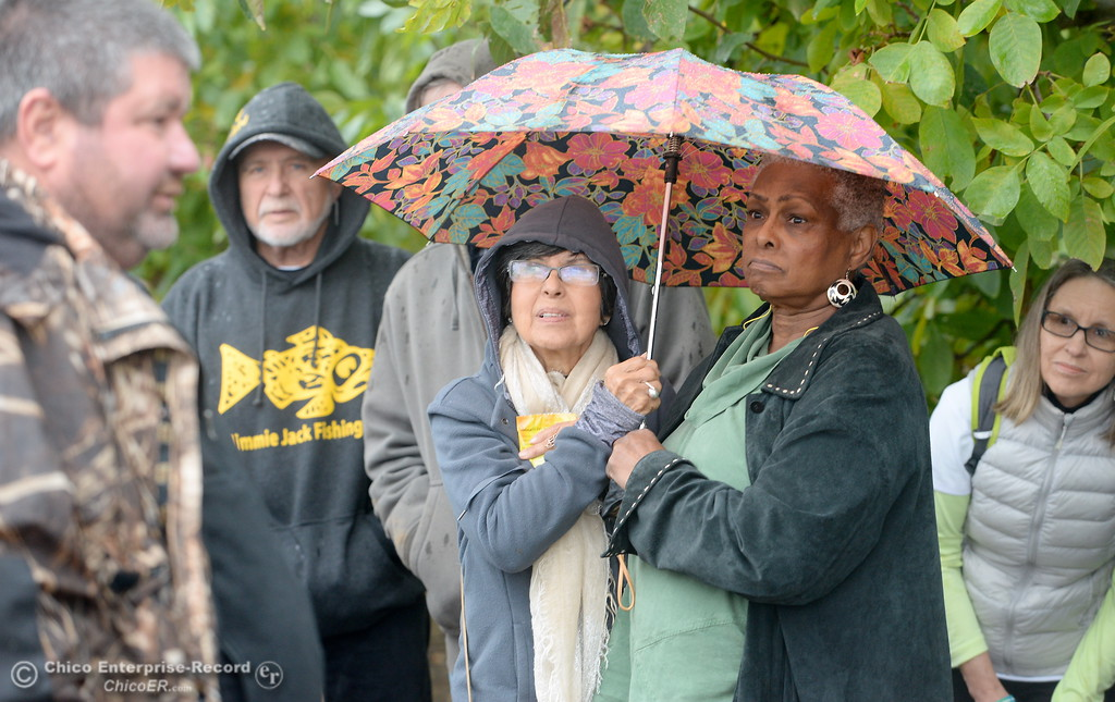 . Yolanda Hittelman and Helen Royal share an umbrella as they listen to Greg Sohnrey talk about orchard culture and management during the 2017 Farm City Bus Tour Wednesday Nov. 8, 2017. (Bill Husa -- Enterprise-Record)