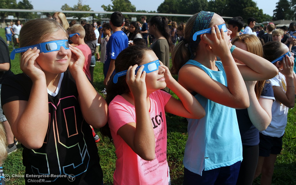 . Sixth graders Morgan Pittman, Brianna Harris and Sarah Kindopp watch the solar eclipse on Monday, Aug. 21, the first day of school at Bidwell Junior High. (Dani Anguiano -- Enterprise-Record)