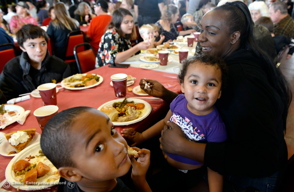 . Sylis Guerrero 5 and Carmen Harris 1, smile as they enjoy their meal with Dejania Harris during the Oroville Rescue Mission\'s community Thanksgiving dinner at the El Medio Fire Station in Oroville, Calif. Wed. Nov. 22, 2017. (Bill Husa -- Enterprise-Record)