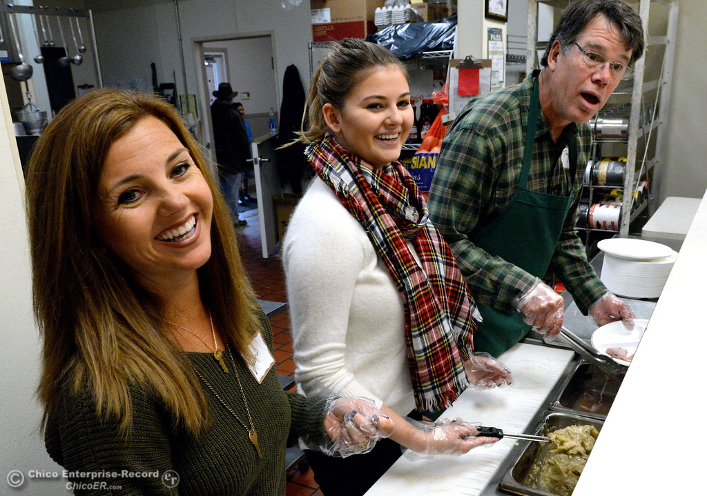 . Left to right, volunteers Jodi Buda, Brianna Buda and Tony Jewett help serve a Christmas meal along with a smile to area homeless during the annual Jesus Center Christmas Dinner in downtown Chico, Calif. Friday Dec. 22, 2017. (Bill Husa -- Enterprise-Record)