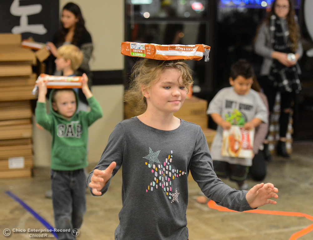 . Amelie Pierce, 10, carries dinner rolls through an obstacle course as volunteers fill baskets with food for Thanksgiving during the annual Basket Brigade Tuesday November 21, 2017 at Azadís Martial Arts Center in Chico, California. (Emily Bertolino -- Enterprise-Record)