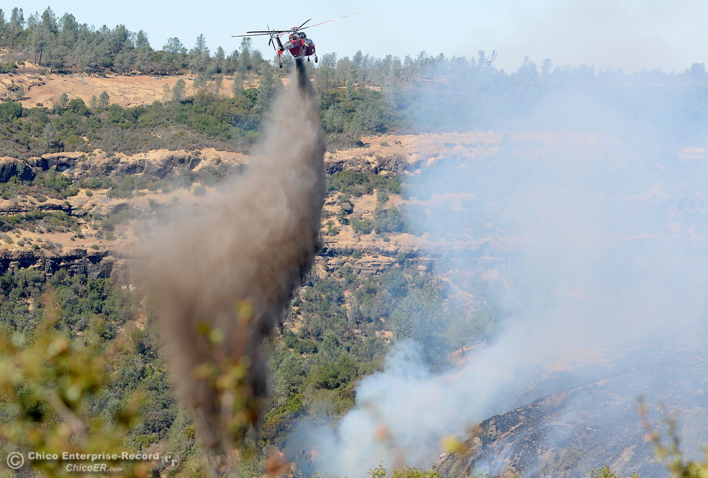 . Helicopters drop retardent while firefighters face steep terrain as they battle a 50 acre fire along Hwy. 32 above Chico, Calif. Monday Sept. 25, 2017. (Bill Husa -- Enterprise-Record)