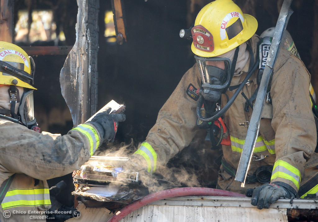 . Firefighters try to salvage items after initial knockdown of a fire at a mobile home at the Pleasant Grove Mobile Home Park located at 6986 Lincoln Blvd. in Palermo Monday, Dec. 4, 2017. One resident, Jesse Rowland injured his arm breaking a window so that he, his mother and a friend could escape through the window. The cause of the fire remains under investigation. (Bill Husa -- Enterprise-Record)