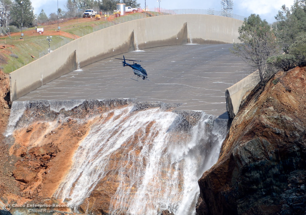 . A helicopter flies in for a closer look after DWR decreased flow on the damaged spillway Monday afternoon.  The extent of the damage is clearly visible with massive chunks of concrete missing from the spillway and a large gully of erosion along the left side Monday Feb. 27, 2017. (Bill Husa -- Enterprise-Record)
