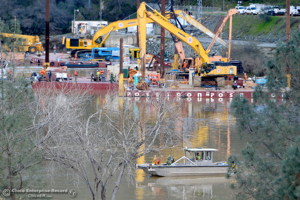 . Barges with heavy equipment are seen near the base of the dam Monday.  DWR decreased water flow on the damaged spillway Monday and the extent of the damage is clearly visible. Monday Feb. 27, 2017. (Bill Husa -- Enterprise-Record)