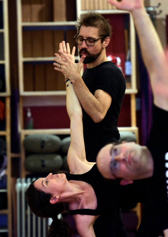 . BOULDER, CO - March 8, 2019: Ty Landrum, helps Pam Sica with her form during a yoga class at The Yoga Workshop on Friday. The Yoga Workshop in Boulder is closing at the end of March. The building it has occupied is being remodeled into office space. (Photo by Cliff Grassmick/Staff Photographer)