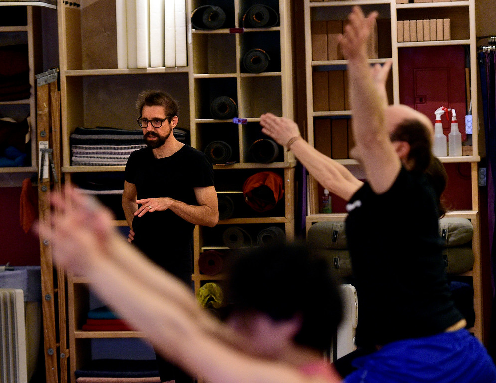 . BOULDER, CO - March 8, 2019: Ty Landrum, left, teaches a yoga class at The Yoga Workshop on Friday. The Yoga Workshop in Boulder is closing at the end of March. The building it has occupied is being remodeled into office space. (Photo by Cliff Grassmick/Staff Photographer)