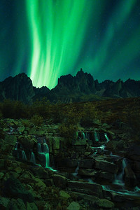 A gorgeous waterfall lit by the Northern Lights