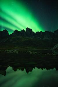 Strong Aurora display over towering granite peaks