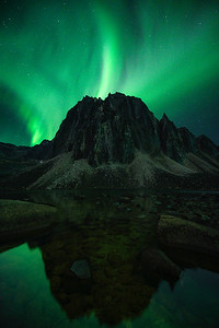 Dancing aurora above a massive tombstone mountain