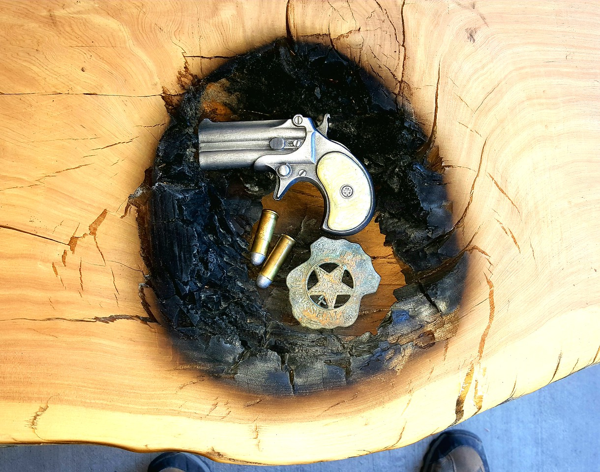 This large burn hole is perfect for the derringer, 45 long colt ammo, and old Marshal's badge.