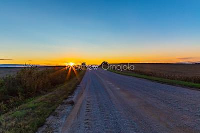Sunset over mega farmland along rural route.