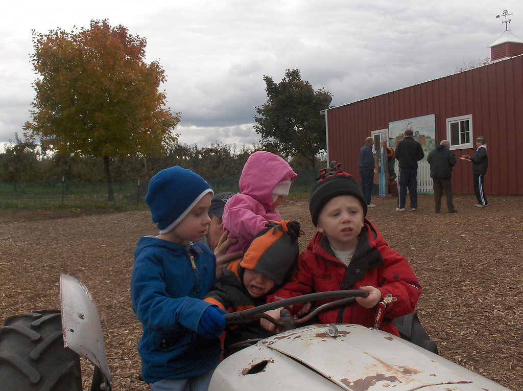 Elliott, Soren, Gavin, and Olive riding the tractors at Edward's Apple Orchard, October 2009