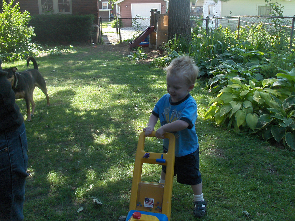 Elliott Swenson helping his mom to mow the lawn.  July 2008