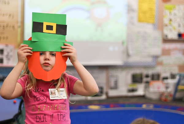 LEANDRA BEABOUT | THE GOSHEN NEWS<br /> Avelyn Weaver, a kindergartener at West Goshen Elementary School, holds up her leprechaun hat as a St. Patrick's Day cartoon plays in the background.
