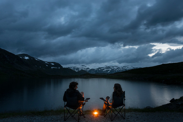 Young couple sitting on camping chairs at the banks of a lake in Norway