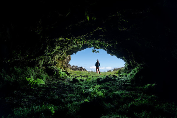 Young woman traveller at the entrance of one of the many lave tube caves on Pico Island, with an amazing vegetation in the foreground and fields with a blue sky in the background.