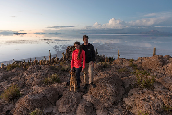 Young couple standing with a dog at the top of Incahuasi Island in Bolivia