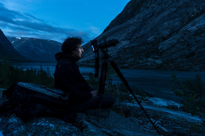 Photographer shooting the glacier river born at the Nigardsbreen glacier in Norway