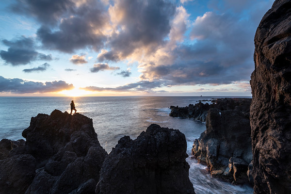 Young woman enjoying a beautiful sunset at the most western point of Europe Fajã Grande from the rocks of the black lava coast