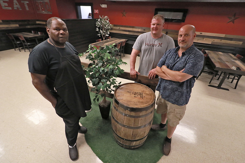 . The Local Spot in Fitchburg is expanding and with a new BBQ restaurant next to their spot on Main Street. They are calling  it TJ\'s BBQ. TJ\'s BBQ Master Bernard Watson, on left, stands with owners Jay Nicosia, center, and Ted Lappas. SENTINEL & ENTERPRISE/JOHN LOVE