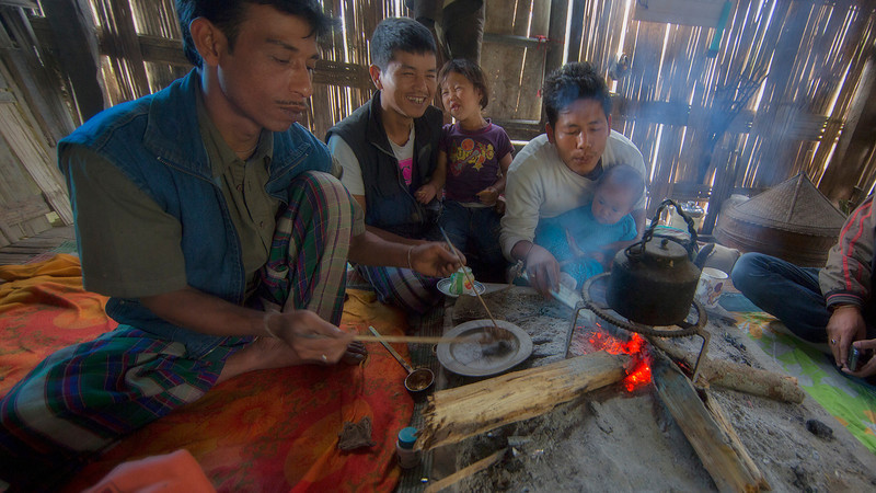 A family gathers by the fire on a wat day.  The nearest man mixes the opium.  It is legal for the Mishmi tribal people to grow enough for their own use (usually a small field or two.