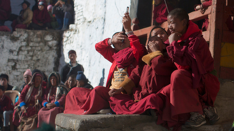Young monks take aim at older monks (on the balcony above)