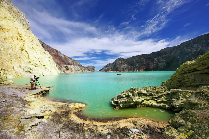 """The film maker, the rubber boat and the acid lake.  Peter films George on the lake (George is the speck in the distance).  For more of this and other Ijen scenes see """"Angry Planet"""" on the Travel Channel or the Weather Channel."""