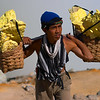A young miner carries his load of sulphur