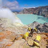 Kawa Ijen, showing the acid lake, the fumarole and a miner carrying a load of sulphur.